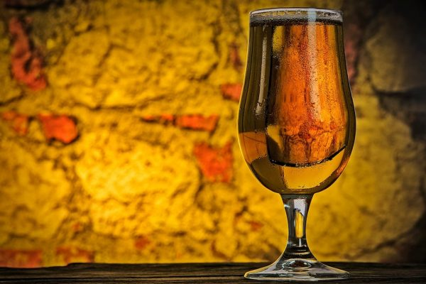 glass of beer in front of yellow background