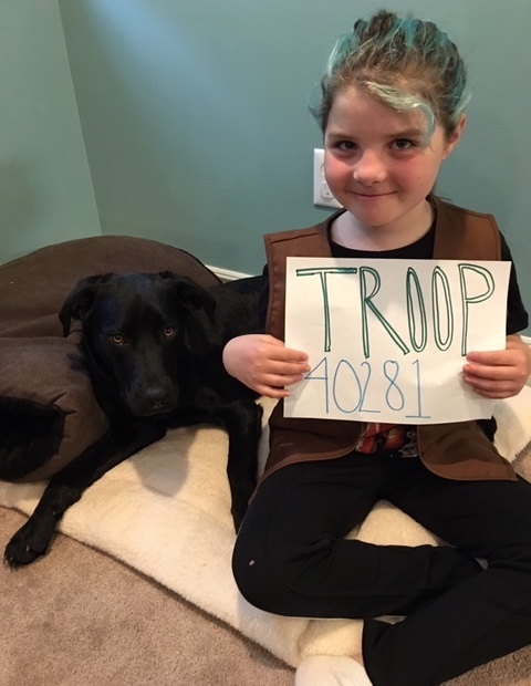 girl scouts visit ER, girl holds sign with troop number